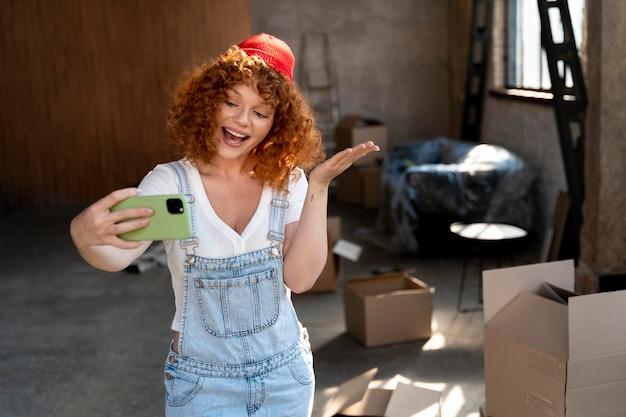 Mujer sonriente tomando selfie con smartphone en su nuevo hogar