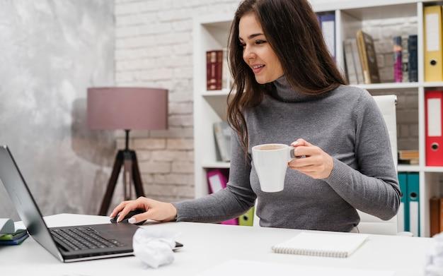 Mujer sonriente trabajando desde casa