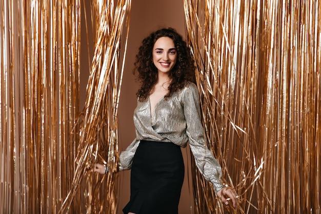 Mujer sonriente en traje plateado posa felizmente sobre fondo dorado