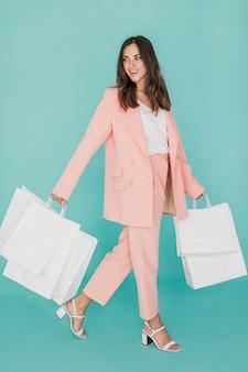Mujer sonriente en traje rosa con redes de compras