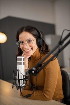 Mujer sonriente transmitiendo en radio con auriculares y micrófono