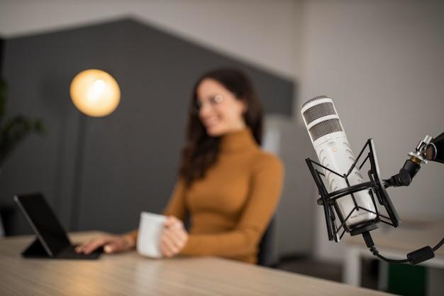 Mujer sonriente transmitiendo en radio con micrófono