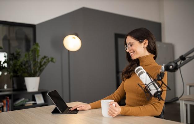 Mujer sonriente transmitiendo en radio con tableta