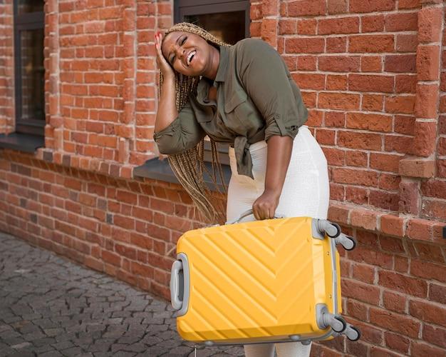 Mujer sonriente tratando de levantar un pesado equipaje amarillo