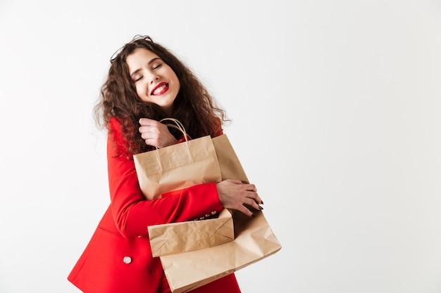 Mujer sonriente de la venta que sostiene bolsos de compras