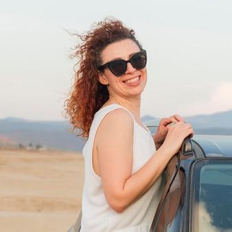 Mujer sonriente en la ventanilla del coche