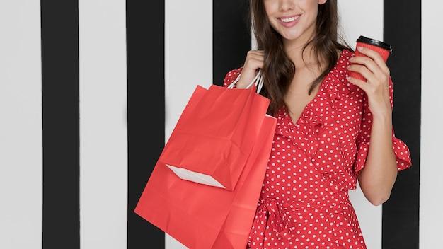Mujer sonriente vestida con café y bolsas de compras