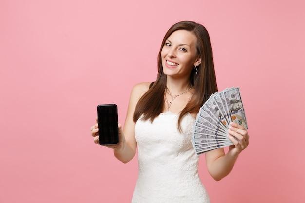 Mujer sonriente en vestido blanco sosteniendo un paquete de un montón de dólares en efectivo, teléfono móvil con pantalla vacía negra en blanco