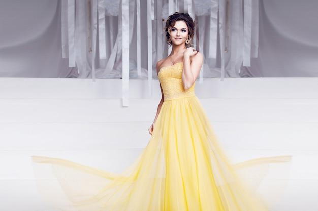Mujer sonriente en vestido de noche amarillo y con hermoso peinado