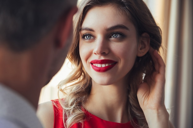 Mujer sonriente en vestido rojo y con labios rojos mirando a su hombre