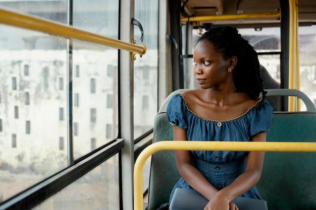 Mujer sonriente viajando en bus plano medio