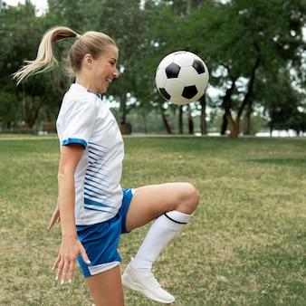 Mujer sonriente de vista lateral entrenando con pelota