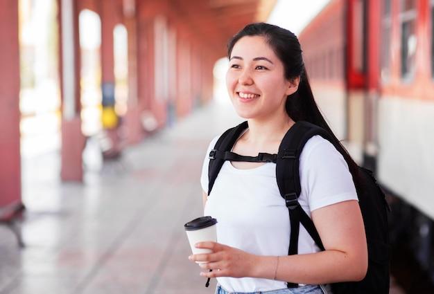 Mujer sonriente de vista lateral en la estación de tren