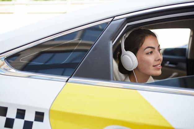 Mujer sonriente en vista lateral de taxi