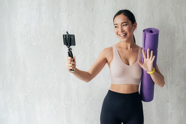 Mujer sonriente vlogueando con su teléfono mientras sostiene una colchoneta de fitness
