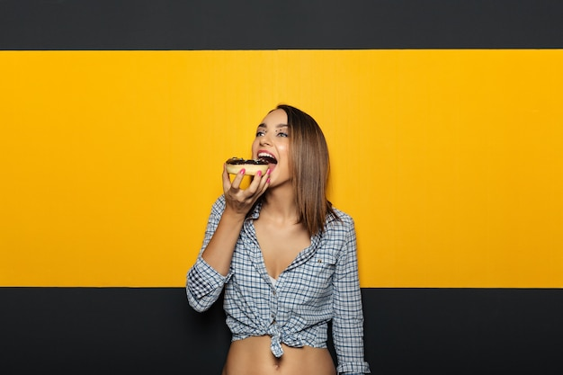 Mujer con sonrisa blanca brillante comer sabroso donut.
