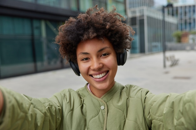 Mujer con sonrisa positiva en la cara toma selfie de sí misma escucha música favorita en auriculares paseos por la ciudad usa chaqueta disfruta de tiempo libre camina al aire libre creats contenido multimedia