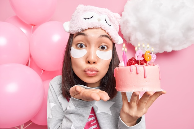 Mujer sopla aire beso en la cámara mantiene los labios doblados sostiene la torta festiva con velas encendidas se prepara para las celebraciones aplica parches de belleza