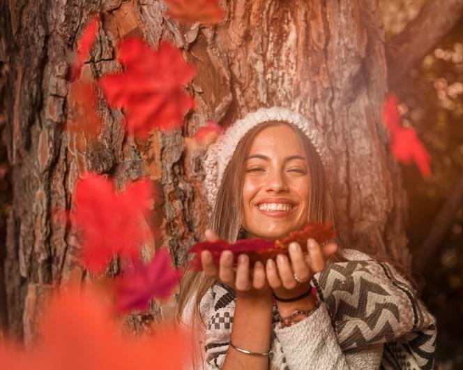 Mujer soplando en hojas de otoño y riendo