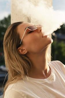 Mujer soplando humo durante fumar vape o narguile
