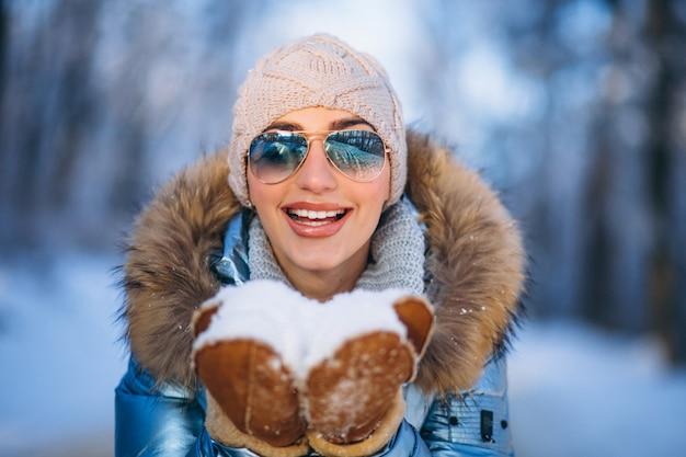 Mujer soplando la nieve de los guantes