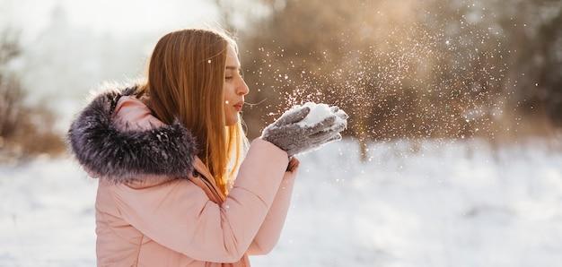 Mujer soplando la nieve de las manos