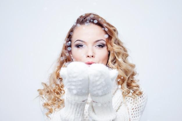 Mujer soplando nieve, niña en cálida bufanda de punto y guantes
