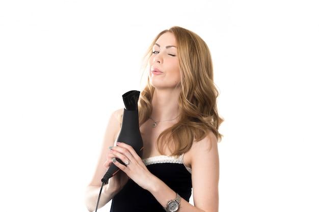 Mujer soplando a la punta de un secador