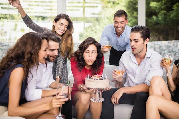 Mujer soplando velas de cumpleaños con un grupo de amigos