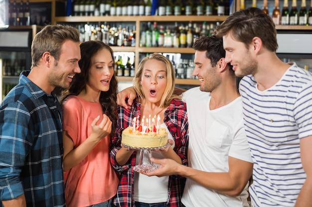 Mujer soplando velas mientras amigos miran