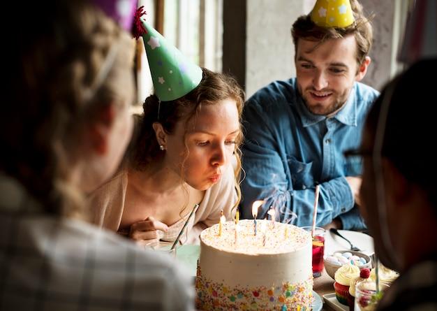Mujer soplando velas en el pastel en su celebración de la fiesta de cumpleaños