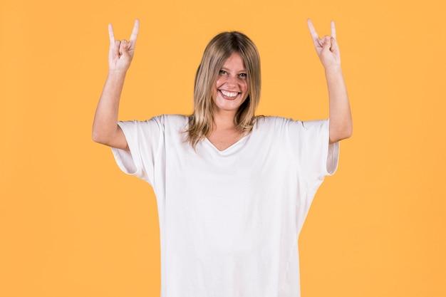 Mujer sorda sonriente que muestra la muestra de la roca delante de la superficie amarilla