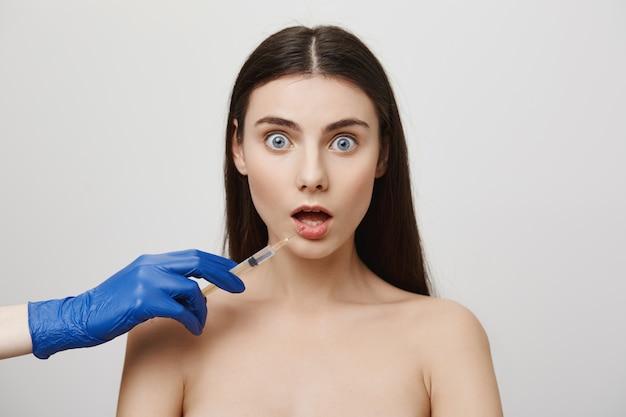 Mujer sorprendida abre la boca y mira preocupada mientras toma la inyección de bottox en el labio