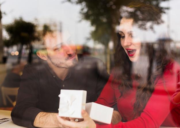Mujer sorprendida abriendo caja de regalo
