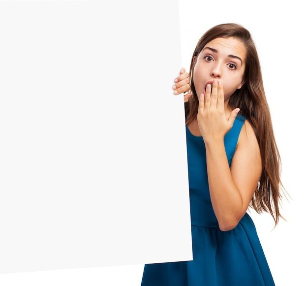 Mujer sorprendida al lado de un cartel