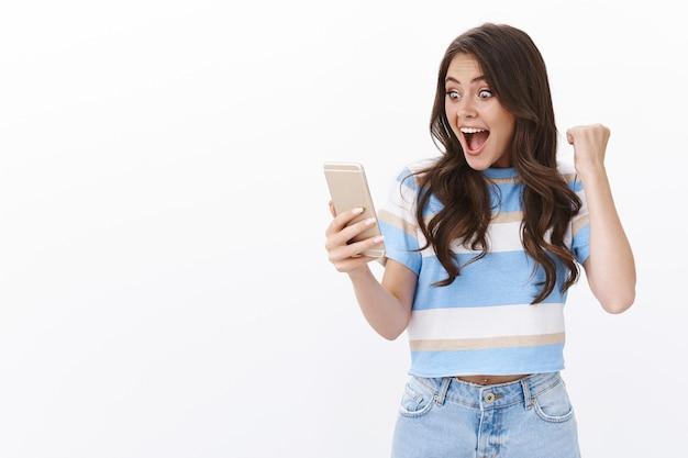 La mujer sorprendida y alegre triunfante recibe noticias positivas, abre los ojos mientras lee el mensaje de texto en el teléfono inteligente, logra el éxito, gana la lotería en línea celebrando
