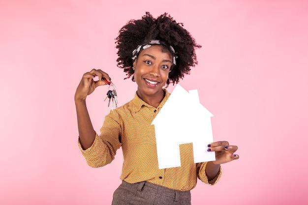 Mujer sorprendida y asombrada sosteniendo la casa de papel y las llaves de la casa, buscando el hogar perfecto, fondo blanco.
