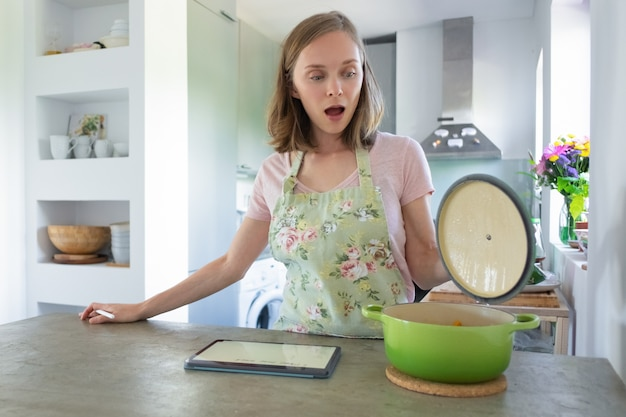 Mujer sorprendida con la boca abierta mirando en una cacerola en su cocina, con tableta en el mostrador. vista frontal. concepto de cocina en casa