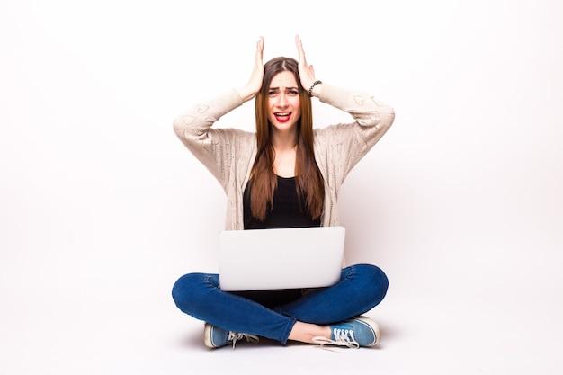 Mujer sorprendida en camiseta y anteojos sentada en el suelo con ordenador portátil y mirando a la cámara sobre gris