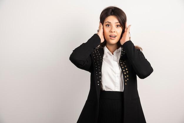 Mujer sorprendida con chaqueta negra se tapó los oídos.