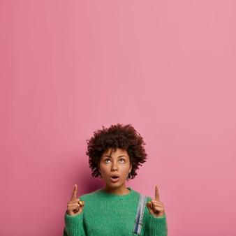 Mujer sorprendida confundida con peinado afro, apunta hacia arriba