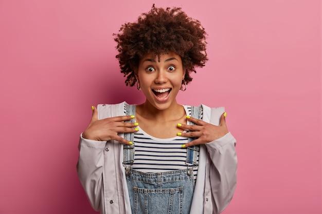 La mujer sorprendida, emocionada y llena de alegría se ve con alegría, mantiene las manos en el pecho, se alegra de recibir la sorpresa, usa ropa informal y anorak, tiene una manicura brillante, abre la boca ampliamente mientras se ríe