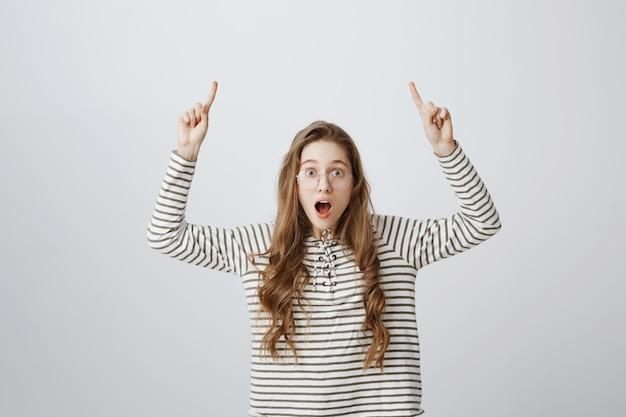 Mujer sorprendida y emocionada mirando impresionado y apuntando con el dedo hacia arriba