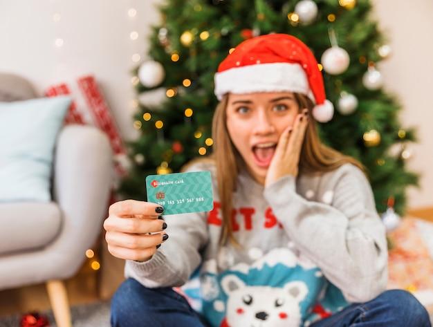Mujer sorprendida en gorro navideño con tarjeta de crédito.