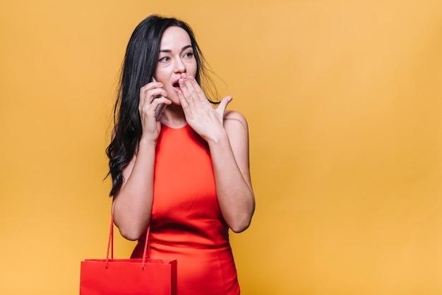 Mujer sorprendida hablando por teléfono mientras compra