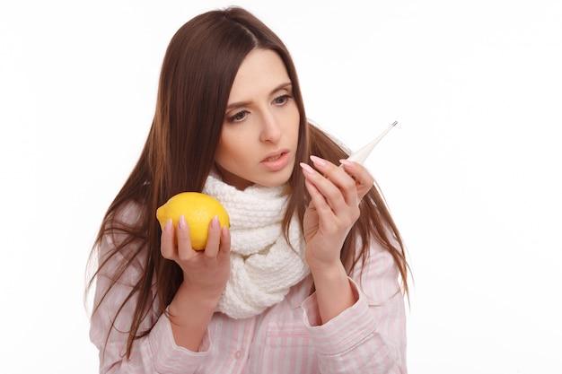 Mujer sorprendida con un limón en la mano y mirando un termómetro