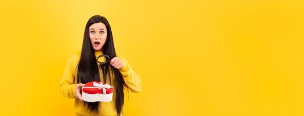 Mujer sorprendida con una lupa y una caja de regalo