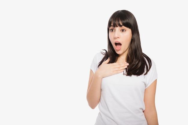 Mujer sorprendida manteniendo la mano en el pecho