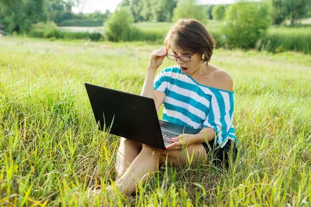 Mujer sorprendida mira el monitor de la computadora portátil mujer autónoma, trabajando en la naturaleza