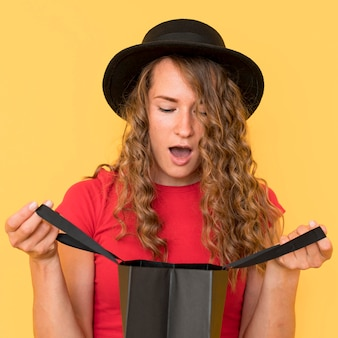 Mujer sorprendida mirando en una bolsa de compras